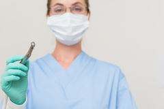 Dentist in blue scrubs holding drill looking at camera Stock Photo