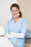 Dentist in blue scrubs smiling at camera Stock Image