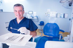 Dentist in blue scrubs smiling at camera holding tools Stock Images