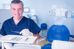 Dentist in blue scrubs smiling at camera holding tools Royalty Free Stock Photos