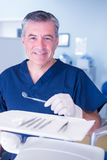Dentist in blue scrubs smiling at camera holding tools Stock Photos