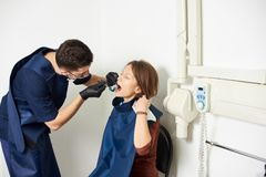 Dentist in a blue uniform is curing the patient in a white dental office stock image