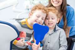 Dentist with boys at the dental officee. Young boys looking at the mirror with toothy smile sitting with dentist at the dental office royalty free stock photo