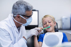 Dentist brushing a young patients teeth Royalty Free Stock Photography