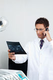 Dentist On Call As He Checks X-Ray Report Royalty Free Stock Photography
