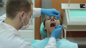 Dentist carry out routine inspection of the patient stock footage