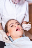 Dentist carrying out a thorough examination. Female patient. Stock Photos