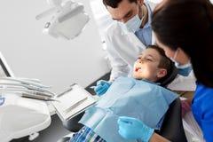 Dentist checking for kid teeth at dental clinic Royalty Free Stock Image