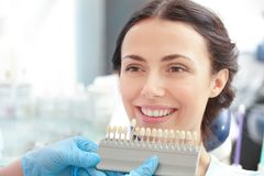 Dentist checking and selecting color of young woman`s teeth Stock Photo