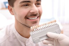 Dentist checking young man`s teeth color royalty free stock photo