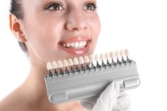 Dentist checking young woman`s teeth color royalty free stock image