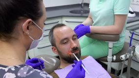 Dentist checks the quality of the dental filling. With special tools stock video footage
