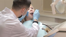 Dentist checks up girl's teeth. Dentist in white medical gown checks up the teeth of a girl. Pretty looking blonde is sitting in the dantist chair while doctor stock video footage