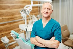 Dentist in clinics. Mature dentist in uniform crossing his arms on chest while looking at camera Royalty Free Stock Photos