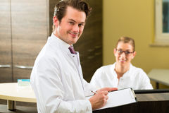 Dentist with clipboard in his surgery Stock Photography
