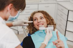 Dentist comparing patient`s teeth shade with samples for bleaching treatment Royalty Free Stock Photos