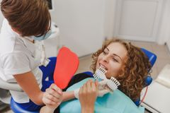 Dentist comparing patient`s teeth shade with samples for bleaching treatment Stock Image