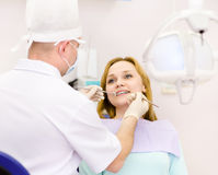Dentist curing a girls teeth in the dental office Royalty Free Stock Image