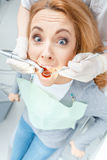 Dentist curing scared patient in clinic Stock Photo