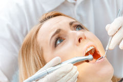 Dentist curing scared patient looking up Royalty Free Stock Photos