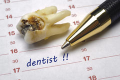 Dentist date. Medicin dentist date in calendar and tooth with dental caries Royalty Free Stock Photography