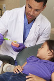Dentist Demonstrating How To Brush Teeth To Young Female Patient Royalty Free Stock Photos