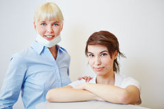 Dentist with dental assistant at desk Stock Photography