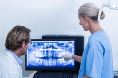 Dentist and dental assistant discussing a x-ray on the monitor Royalty Free Stock Image