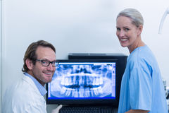 Dentist and dental assistant discussing a x-ray on the monitor Royalty Free Stock Photo