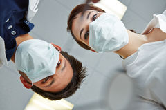 Dentist and dental assistant looking at patient Stock Images