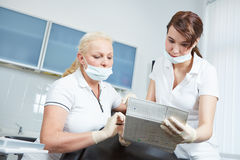 Dentist and dental assistant reading medical recor Royalty Free Stock Image