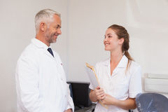 Dentist and dental assistant smiling at each other Royalty Free Stock Photography