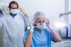 Dentist and dental assistant wearing surgical mask Stock Image