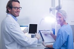 Dentist and dental assistant working on digital tablet Stock Images