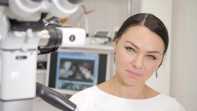 The dentist directs modern microscope to the patient. Beautiful woman doctor dentist. Young African American male. Young beautiful girl doctor dentist. Young stock video
