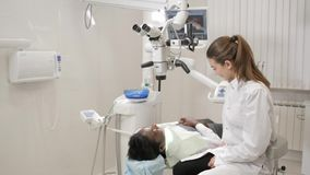 The dentist directs modern microscope to the patient. Beautiful woman doctor dentist. Young African American male. Young beautiful girl doctor dentist. Young stock footage