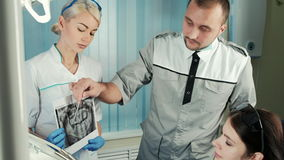 Dentist discuss with his patient x-ray, which nurse hold. stock footage