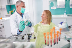 Dentist discuss about intervention with patient Royalty Free Stock Image