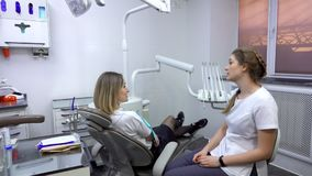 Dentist discusses dental treatment with patient. Dental clinic stock footage