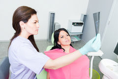 Dentist doctor and patient examining teeth xray. In dental office stock photo