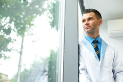 Dentist Doctor Stands Near Window and Thinks about Clinic Future Royalty Free Stock Image