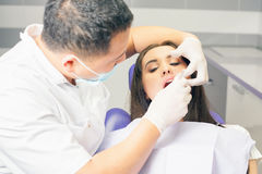 Dentist doctor treats teeth patient girl in dental office royalty free stock photos