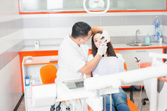 Dentist doctor treats teeth patient girl in dental office Royalty Free Stock Images