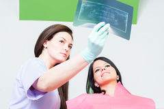 Dentist doctor and woman patient checking xray. Female dentist doctor and women patient checking teeth xray royalty free stock photos