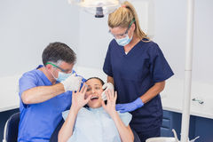 Dentist doing injection and patient protesting Stock Images
