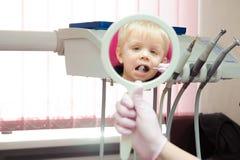 Dentist doing regular dental check-up to little boy. royalty free stock images