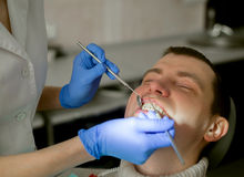 Dentist is doing treatment procedures in dental office. Dentist is doing treatment procedures stock photo