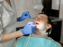 Dentist is doing treatment procedures in dental office. Dentist is doing treatment procedures stock photos