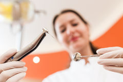 Dentist with a drill and medical mirror. Female dentist using a drill for the root canal treatment Stock Image