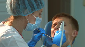 The dentist drills the tooth to the young guy. 2 Shots stock video footage